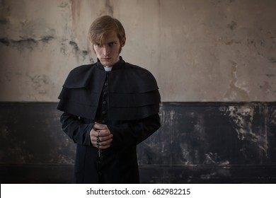 Portrait of handsome young catholic priest looking at you. Prayer