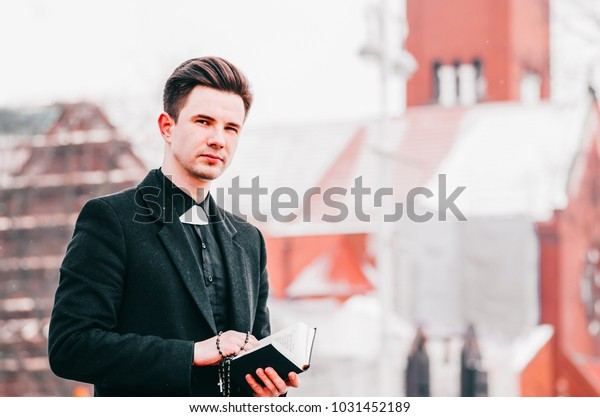 Portrait of handsome young catholic priest reading the prayer book against church background.