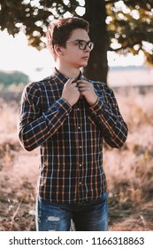 Portrait of a handsome young caucasian man wearing eyeglasses dressed in shirt with plaid checkered flannel print outdoors beautiful sundown. Looking aside.