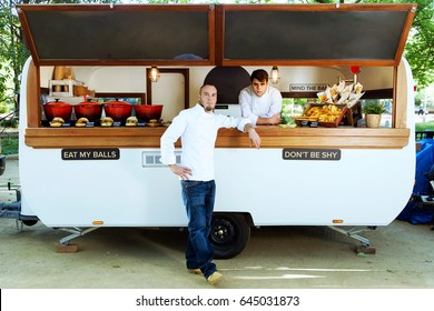 Portrait of handsome young chef looking at camera and smiling in a food truck.