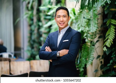 Portrait of a handsome, young Chinese Asian professional businessman in a suit against a wall with green plants during the day. He is relaxed, confident and smiling.