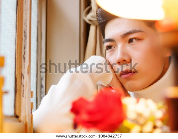 Portrait of a handsome young Chinese man sitting in cafe and looking aside with chin in hand.