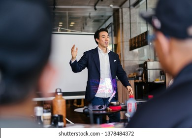 Portrait of a handsome, young and confident business man in a suit giving a presentation to an audience in a stylish cafe or coworking space. He is gesturing with his arm animatedly as he presents.