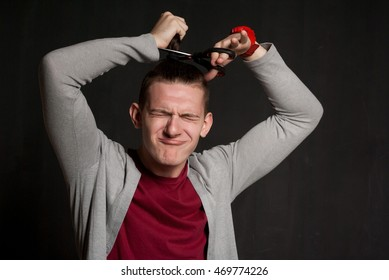 Portrait of handsome young dark-haired man cutting hair with scissors wearing casual clothes. Isolated on black background