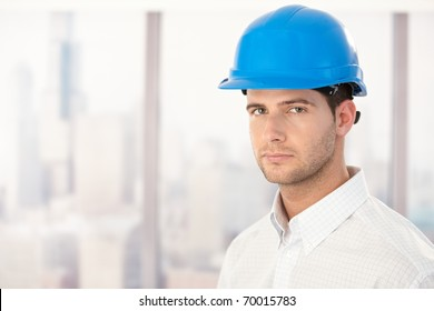 Portrait of handsome young engineer wearing hardhat.?