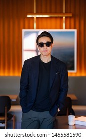Portrait of a handsome, young and fit Chinese Asian man in a casual suit and sunglasses. He is standing and smiling in a warm, well-decorated room during the day. He is neat, dashing and confident.