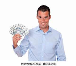 Portrait of a handsome young guy holding his dollars while smiling at you on isolated studio