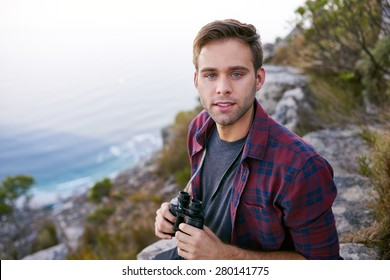 Portrait of a handsome young guy holding binoculars while sitting outdoors on a mountain trail with ocean visible in the background