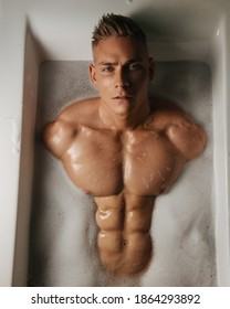 Portrait of handsome young guy with six pack abs lying in bath with foam