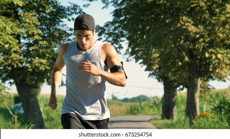 Portrait of a handsome young guy sportsman, holding a phone, smiling, wearing sports clothes, running outside. Concept: love sports, healthy lifestyle, be beautiful, muscles, happy, burn calories.