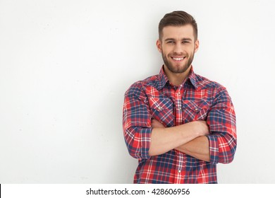 Portrait of handsome young guy standing against white wall.