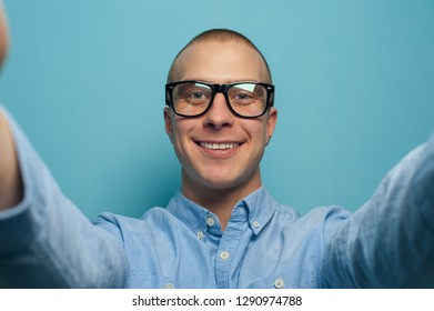Portrait of a handsome young guy student or manager taking a selfie on a tablet or smartphone. Space for advertising