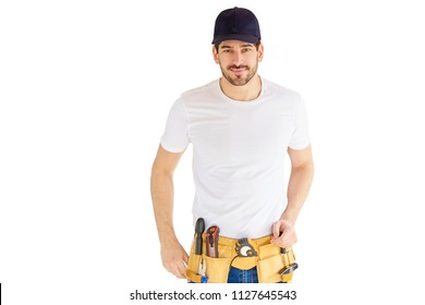 Portrait of handsome young handyman wearing baseball cap and tool belt while standing at isolated white background with copy space.