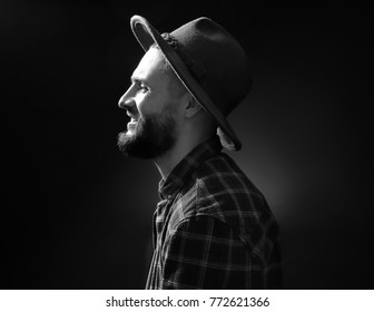 Portrait of handsome young hipster man on black background