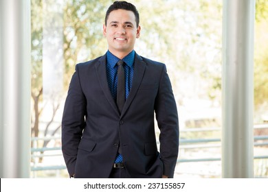 Portrait of a handsome young Hispanic businessman smiling at work