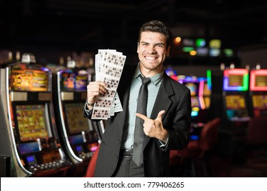 Portrait of a handsome young Hispanic man holding a bunch of lottery and bingo tickets and winning in a casino