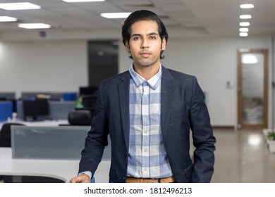 Portrait of handsome young Indian businessman standing against corporate office background.