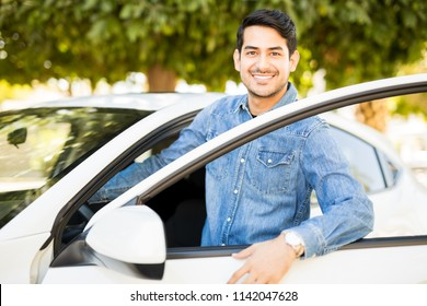 Portrait of handsome young latin man getting inside his car, making an eye contact and smiling