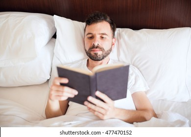 Portrait of a handsome young Latin man reading a book in his bed, early in the morning