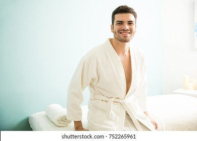 Portrait of a handsome young Latin man wearing a bath robe and waiting to get a massage in a spa