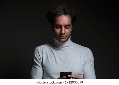 Portrait of handsome young male with curly hair, he holding his phone and feel happy