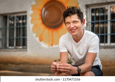 Portrait of handsome young male sitting. City wall with windows and a big yellow flower decoration in the background.