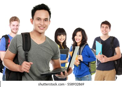 Portrait of handsome young male student with laptop and friends at the background