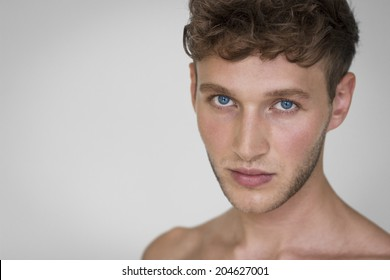 Portrait of handsome young man against neutral background.
