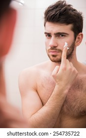 Portrait of a handsome young man is applying shaving cream to his face.