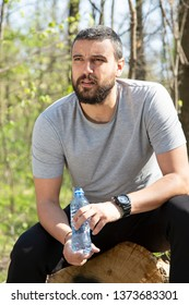 Portrait of handsome young man athlete drinking water in forest