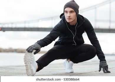 Portrait of handsome young man athlete stretching legs and working out outdoors