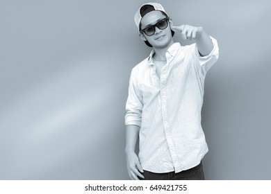 Portrait handsome young man. Attractive handsome cool guy is pointing finger to favorite thing that make him satisfied and happy, smile face. He wears jeans. beautiful back and white photo, copy space