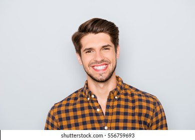Portrait of handsome young man with beaming smile on gray background