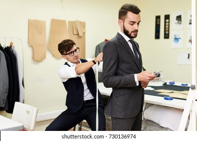 Portrait of handsome young man being fitted in bespoke suit by tailor in traditional atelier studio