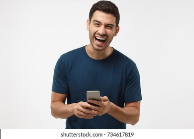 Portrait of handsome young man in blue t-shirt, holding smartphone, looking at camera and laughing, isolated on gray background