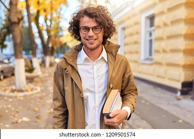 Portrait of handsome young man with books outdoors. College male student carrying books in college campus in autumn street background. Smiling guy with glasses and curly hair posing with books outside