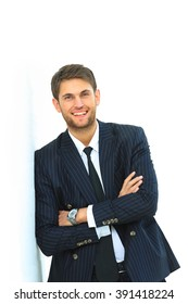 Portrait of a handsome young man in a business suit. standing near the wall