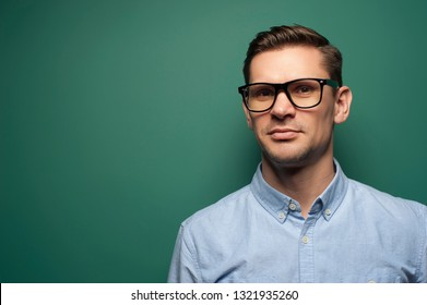 Portrait of a handsome young man businessman in a blue shirt and stylish glasses looking at the camera against a green background. Place for text