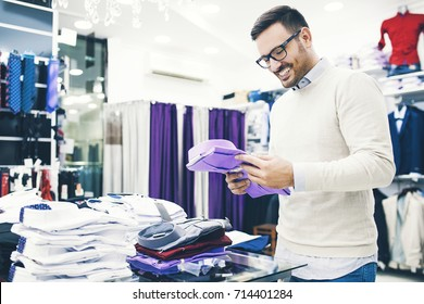 Portrait of handsome young man buying clothes in the store.