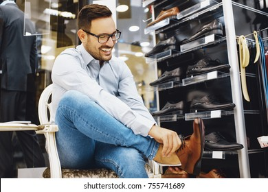Portrait of handsome young man buying shoes in the store.