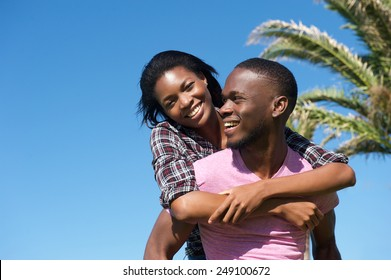 Portrait of a handsome young man carrying attractive woman on his back outdoors