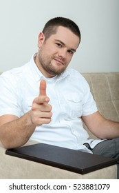 Portrait of handsome young man in casual shirt keeping arms crossed looking at the camera while sitting against a wall in an home.