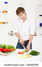portrait of handsome young man cooking slice, cutting green pepper, tomato in the kitchen, cooking, prepare vegetable salad, happy smile