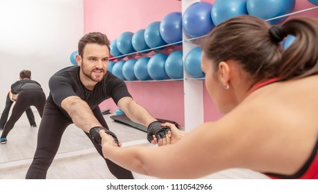 Portrait of a handsome young man doing stretching exrcises in a gym together with his girlfriend.