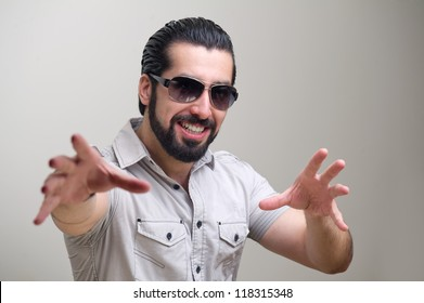 Portrait of a handsome young man doing hand gestures and smiling