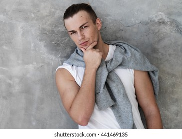 Portrait of a handsome young man, fashion model. Posing over grey wall.