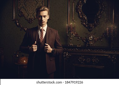 A portrait of a handsome young man in a formal suit posing in a luxury apartments with classic interior. Men's beauty, fashion.