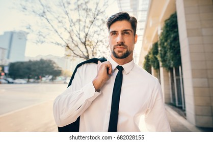 Portrait of handsome young man in formal wear walking outside on the city street. Caucasian businessman walking down the street.