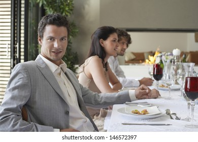Portrait of handsome young man with friends having formal dinner party