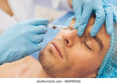 Portrait of handsome young man getting an injection in face, lying with closed eyes, close-up
